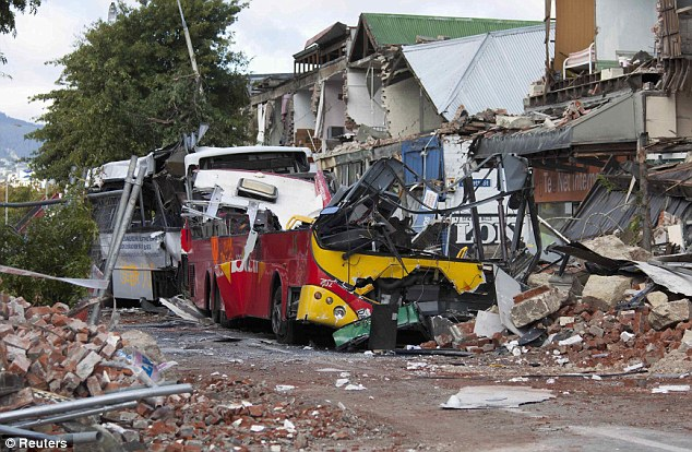 Devastation: Two wrecked buses were crushed on Colombo Street, the main road through Christchurch