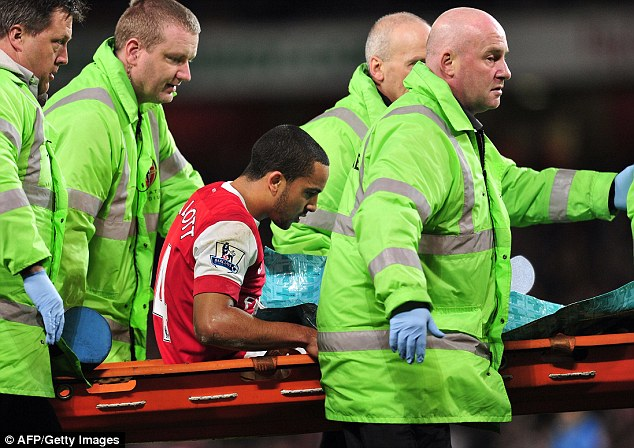 Nightmare: Theo Walcott was carried off on a stretcher in the win over Stoke