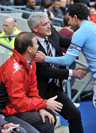 I remember you! Mark Hughes and Carlos Tevez greet each other at Eastlands