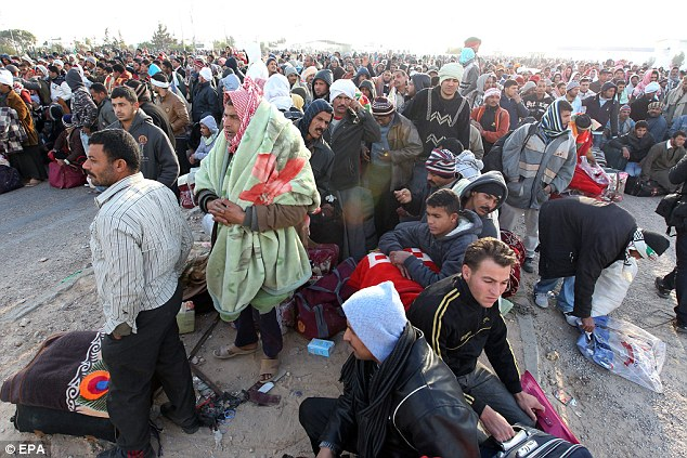 Exodus: Egyptian residents wait for a bus at the Ras Jdir border crossing with Tunisia