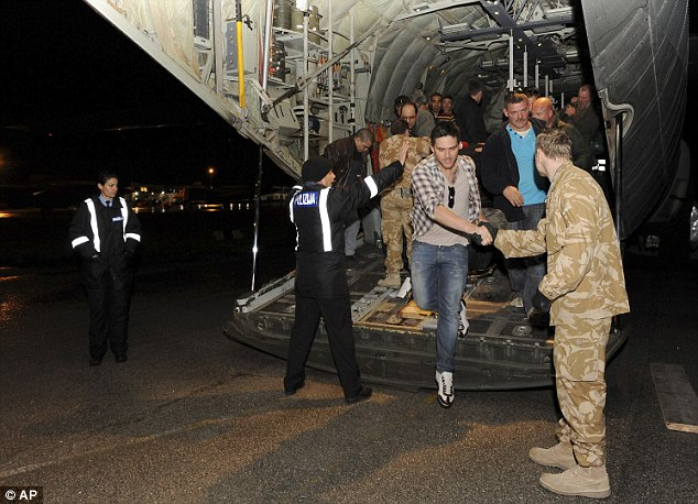 Daring: Oil workers shake hands with RAF ground crew after they were dramatically rescued from the Libyan desert
