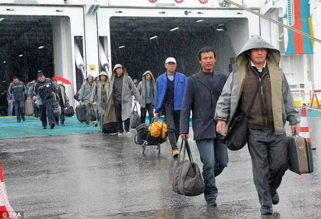 Fleeing: Chinese nationals disembark from a Greek ferry in Heraklion. Around 100,000 people are believed to have left Libya since the uprising began