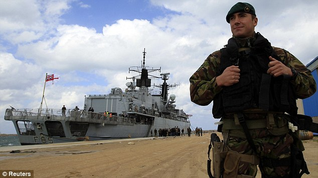 Evacuation: A Royal Marines Commando stands in front of the HMS Cumberland at Benghazi port
