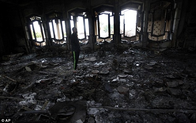 Former stronghold: A Libyan man stands in the burned out house of Gaddafi at Al-Katiba military base in Benghazi