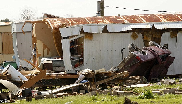 Devastation: An overturned vehicle lies next to a wrecked trailer. The tornado destroyed 100 homes