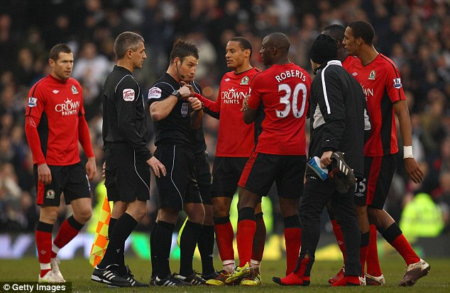 Livid: Blackburn players surround Clattenburg after the final whistle at Craven Cottage