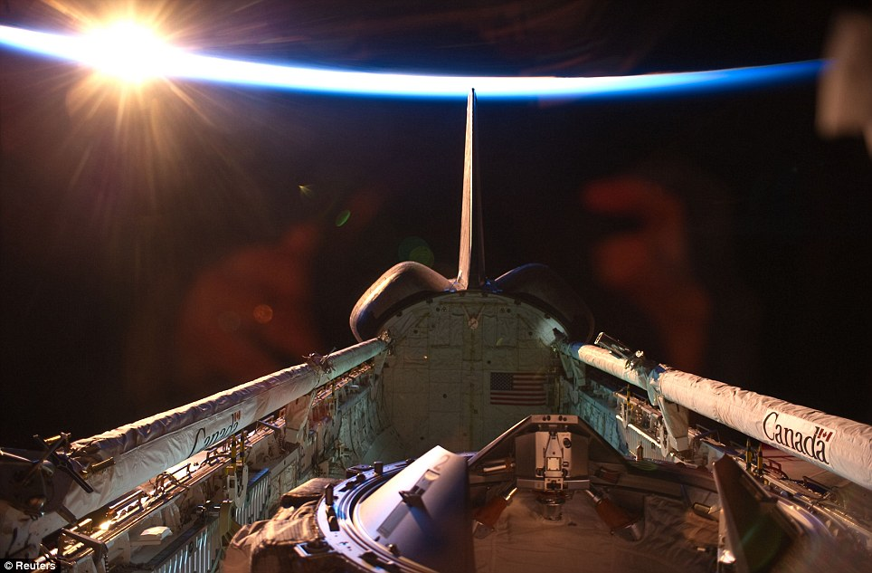 Final preparations: An orbital sunrise brightens this view of Discovery's vertical stabiliser, docking mechanism, remote manipulator system / orbiter boom sensor system and payload bay