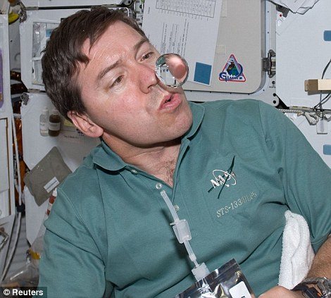 Astronaut Michael Barratt watches a water bubble float freely near him on the middeck of space shuttle Discovery