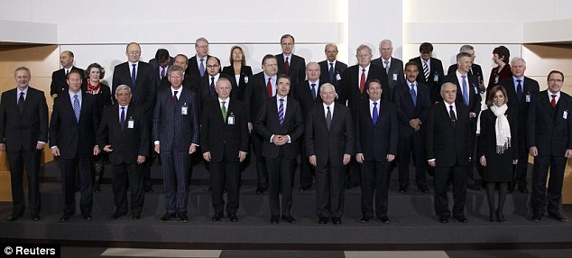 No no-fly zone without a UN resolution: NATO Secretary-General Anders Fogh Rasmussen poses for a family photo with defence ministers following a meeting at the Alliance headquarters in Brussels