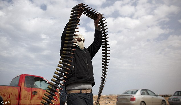 Moving on out: A member of the Libyan volunteer army prepares to load ammunition on to a van