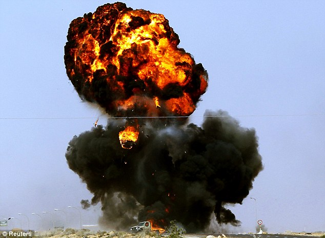 Battle: A rebel vehicle is hit by a shell fired by soldiers loyal to Libyan leader Muammar Gaddafi, during a battle along the road between Ras Lanuf and Bin Jiwad today.