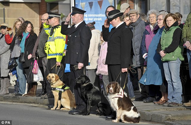 Standing to attention: Police and Prison Service dogs with their handlers who salute as the cortege for Lance Corporal Liam Tasker approaches