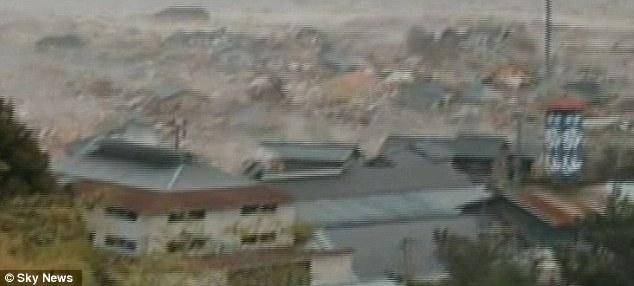 Showing Tsunami waves crashing into and moving building