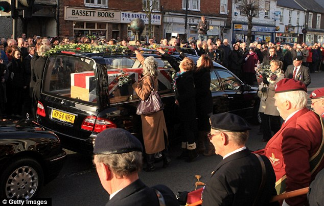 Tributes: Mourners place flowers on the hearse carrying the body of Lance Corporal Liam Tasker as it passes along the High Street in Wootton Bassett, yesterday