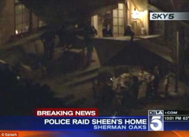Drama: Footage from an American news channel shows police officers at the scene of Charlie Sheen's Beverly Hill's mansion for what has been described as a pre-planned raid
