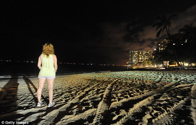 Evacuated: A woman stands on the deserted beach at Waikiki and watches as the first wave hits the shore