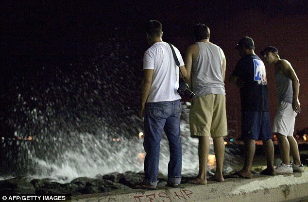 Escape: Four men stand on the beach in Honolulu as tsunami waves roll in. Scientists say no serious damage was caused, but low-lying areas were evacuated