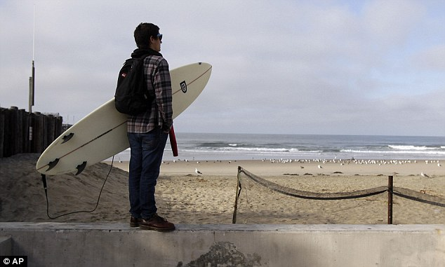Unperturbed: Surfer Mark Fontes, watches the waves at  Newport Beach, California. Some surfers have defied warnings and taken to the waves