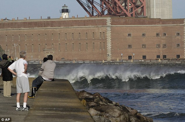 Watching and waiting: A group of people in San Francisco look on as a wave hits near Fort Port under the Golden Gate bridge. The effect of the tsunami has been less severe than first thought