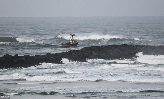 Rough seas: A boat moves out into the swirling sea at Yaquina Bay, Oregon. Sirens blared to warn residents to evacuate to higher ground, but some chose to stay behind