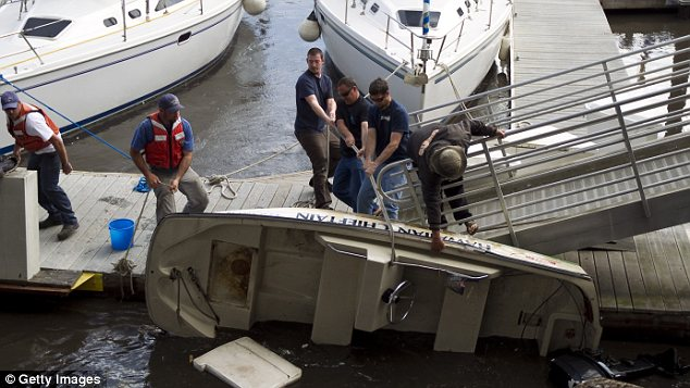 Damage: A group of men try to save a Boston Whaler boat after it tipped over from a tsunami surge in a harbour in Santa Cruz, California