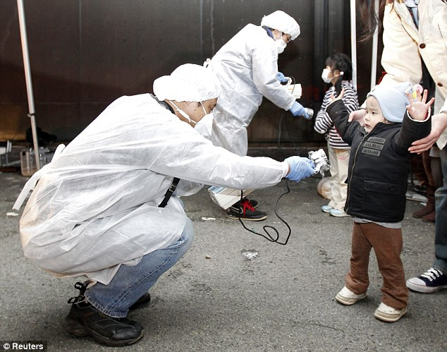 Checks: Officials carry out radiation tests on children who were evacuated from the area near Fukushima