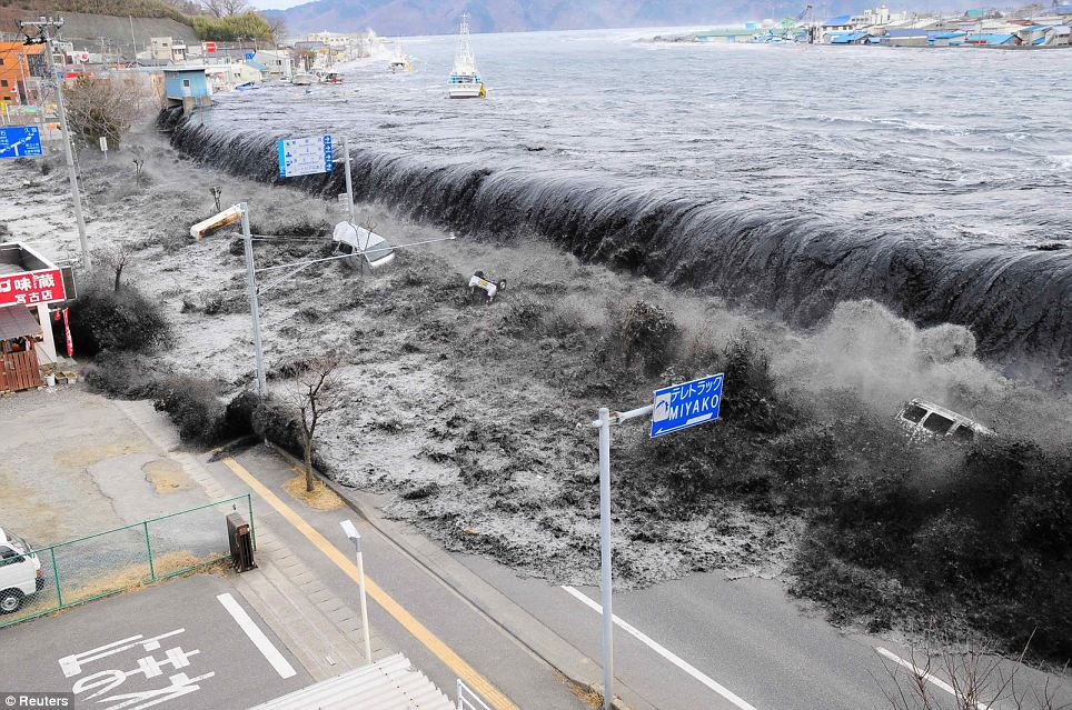 The wave from a tsunami crashes over a street in Miyako City in an incredible picture taken on Friday but only just released