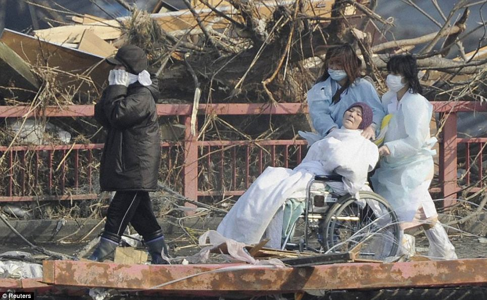 A patient is evacuated from a destroyed hospital in Otsuchi Town, Iwate Prefecture