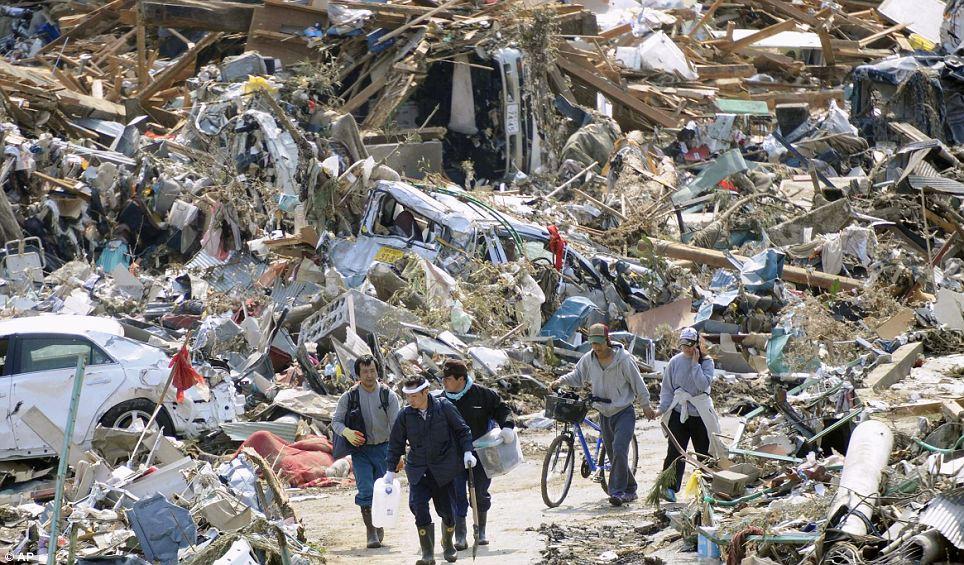 People walk through the rubble in Rikuzentakakata, Iwate Prefecture