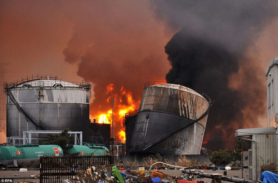 Flames and smoke  rise from a petroleum refining plant next to a heating power station in Shiogama, Miyagi Prefecture