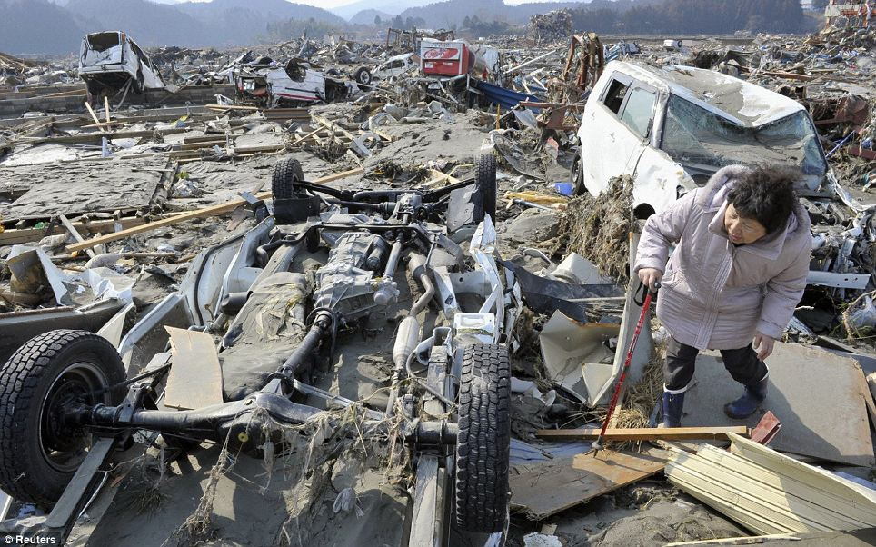 A woman searching for her missing husband looks under an overturned truck after an earthquake and tsunami struck Minamisanriku