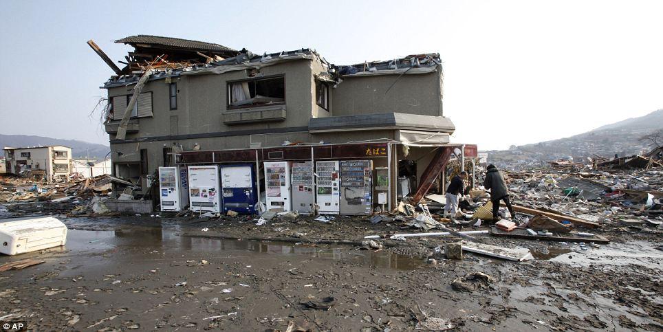 Men search through a rare standing store in house in Ofunato, Iwate Prefecture