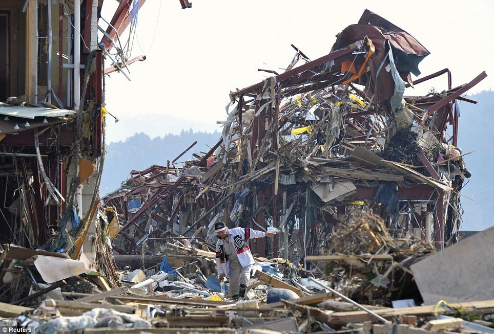 The size of the clear-up job is huge, as shown by this lone figure in among rubble piled high in Minamisanrikucho, Miyagi Prefecture
