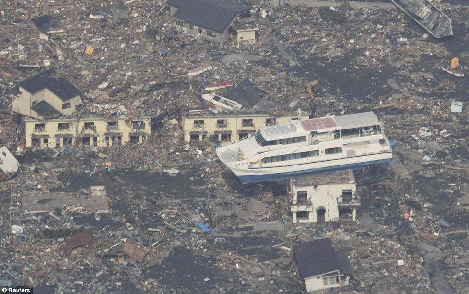 Indescribable force: The wave carried a ferry inland leaving perched on top of a house in Otsuchi