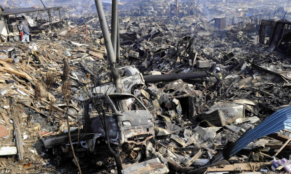 Devastation: Destroyed cars and houses hit by the tsunami and subsequent fire in Kesennuma, Miyagi prefecture, northern Japan
