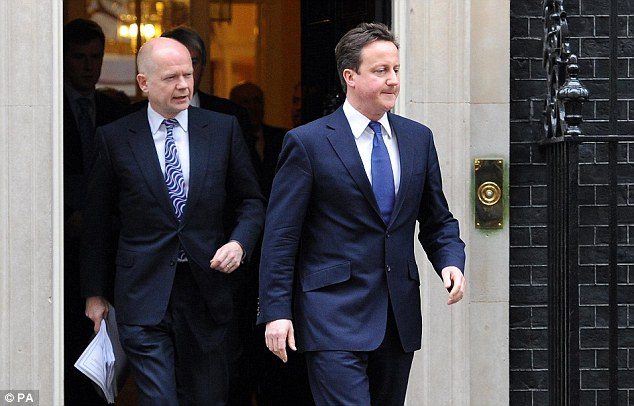 Tough talk: David Cameron (right) and Foreign Secretary William Hague leave Downing Street today after an emergency Cabinet meeting on the Libyan crisis
