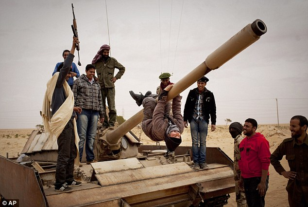 Frontline: Libyan rebels pose on a tank captured from Government forces near Sultan, south of Benghazi