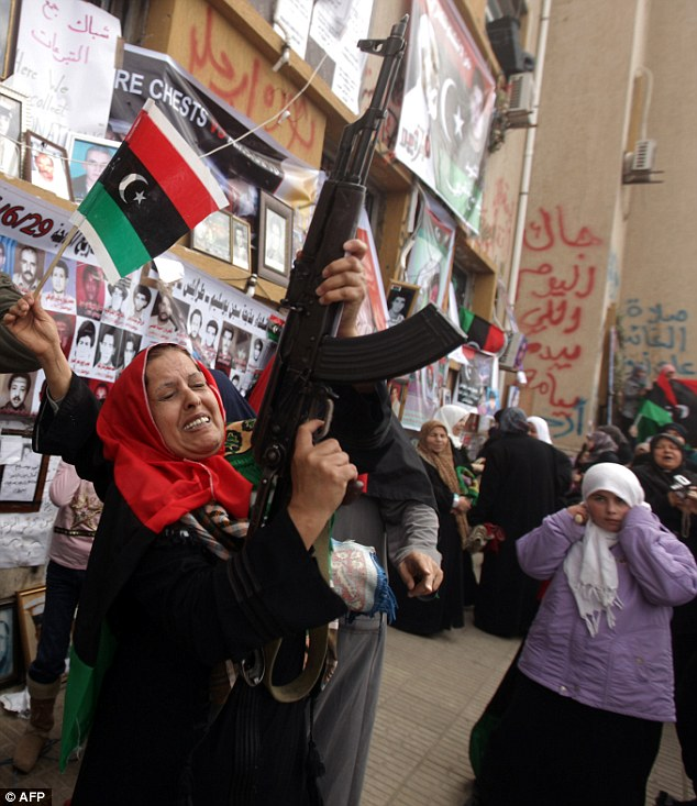 Celebration: A woman fires into the air after the UN agreed to air strikes against Gadaffi