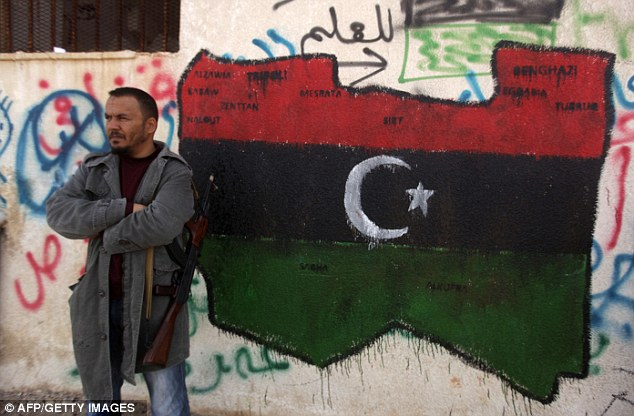 Fight for you right: A rebel stands next to map of Libya painted on a wall in the center of Benghazi