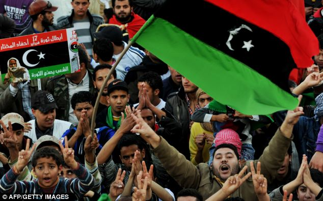 Libyan anti-government protesters chant slogans and wave the revolution flag