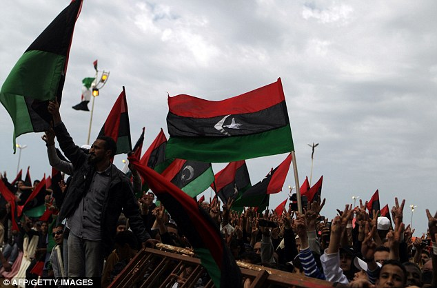 Flying the flag: Libyan anti-government protesters wave the flag of the former Libyan monarchy as they gather in the eastern rebel-held city of Benghazi