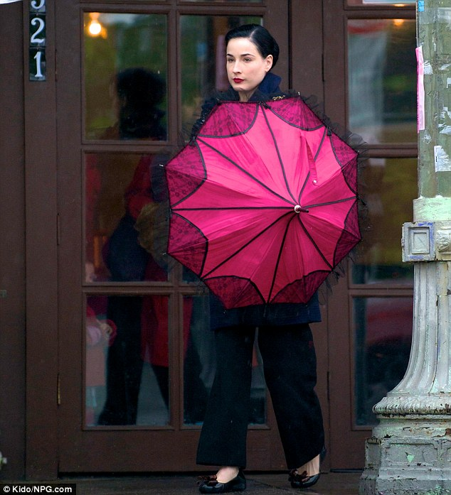 Flawless: The burlesque beauty looked stunning in an all black outfit with a bright pink vintage umbrella