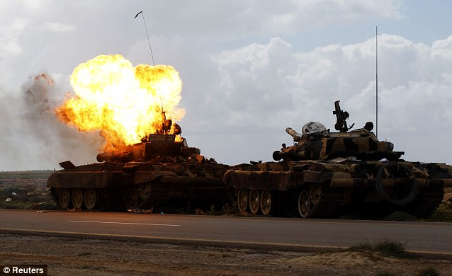 Smashed: A tank belonging to forces loyal to Libyan leader Muammar Gaddafi burns after an air strike by coalition forces