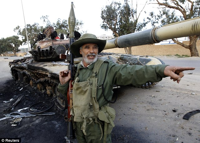 Saved: An elderly rebel fighter poses next to tank from the Gaddafi loyalist armoured column devastated by air attacks