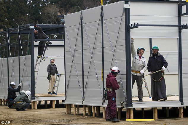 Temporary: Japanese construction workers build shelters for evacuees in Rikuzentakata, which was destroyed by the tsunami