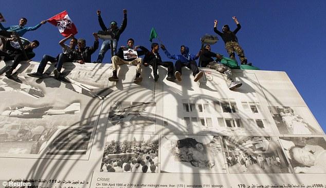 Defiant: Pro-Gaddafi Libyans shout slogans as they stand on a wall in Bab Al- Aziziyah close to  Gaddafi's hideaway