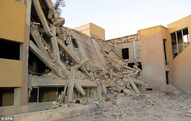 Smashed: The rubble after a missile totally destroyed an administrative building of Gaddafi's residence in Tripoli yesterday
