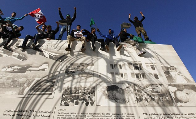 On guard: Supporters of Gaddafi shout slogans as they stand and sit on a wall outside his personal compound, which is just yards from his official residence in Tripoli