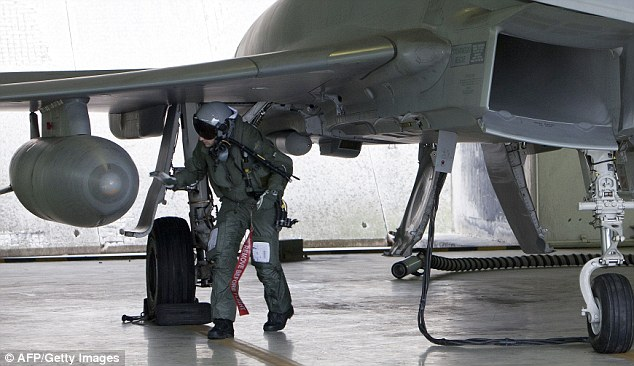 Pre-flight check: An Italian pilot checks over his Typhoon jet which may take part in the 'Odyssey Dawn' raids
