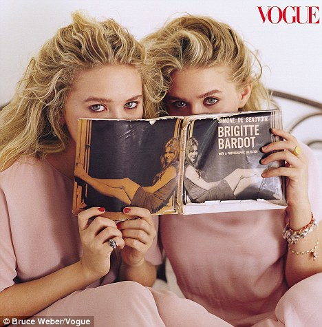 Pretty in pink: The blonde-haired sisters also posed for famed photographer Bruce Weber in dusty pink dresses from their own label, The Row, while they peeped over an antique Brigitte Bardot book